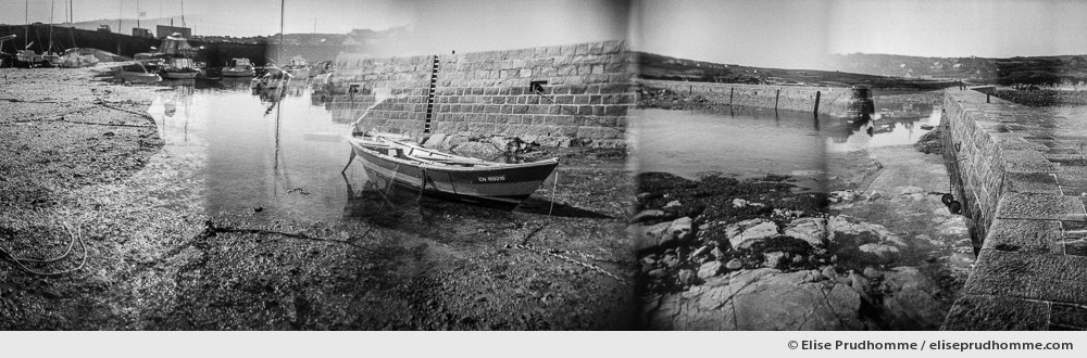Black and white photograph of boats moored at low tide on the jetty of Port Lévi, Fermanville, France. Analog photography series entitled Lieux-dits by Elise Prudhomme.