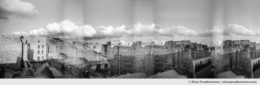 Black and white panoramic photograph of Parisian rooftops and sky, Paris, France. Analog photography series entitled Lieux-dits by Elise Prudhomme.