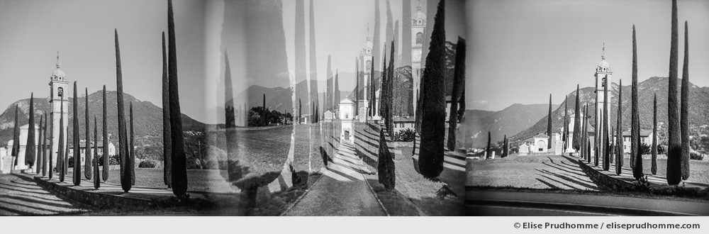 Black and white panoramic photograph of an avenue of cypress leading to a church, Tuscany, Italy. Analog photography series entitled Lieux-dits by Elise Prudhomme.
