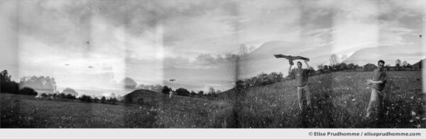Black and white panoramic photograph of a young man flying a Chinese kite in Saint Ours, France. Analog photography series entitled Lieux-dits by Elise Prudhomme.
