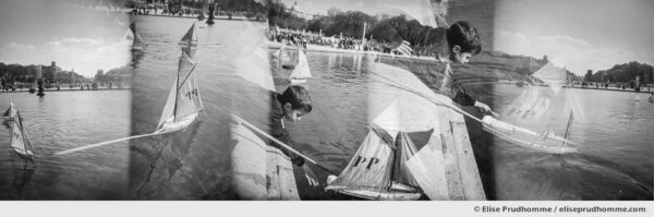Black and white panoramic photograph of a boy sailing his boat in the basin at Luxembourg Garden, Paris, France. Analog photography series entitled Lieux-dits by Elise Prudhomme.