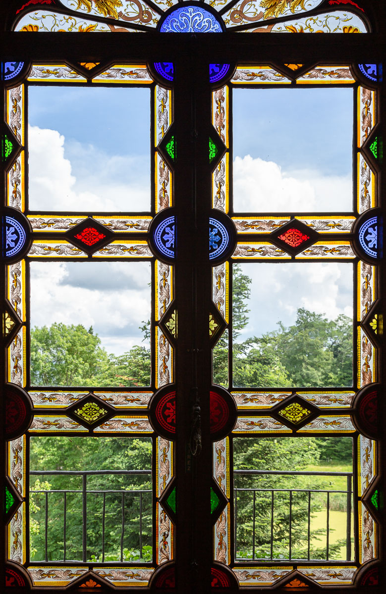 Stained glass window and landscape behind at the Chateau de Maulmont near Vichy, France.