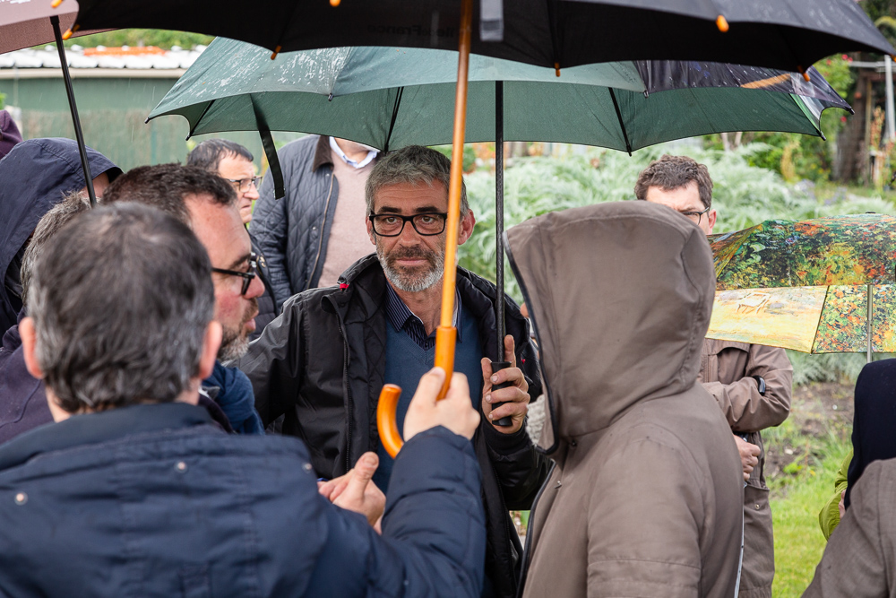 Chief gardener Franck Ponthier under an umbrella during the inauguration of the Urban Farm of Saint-Denis on May 11, 2019.  L'inauguration de la Ferme Urbaine de Saint-Denis le 11 mai 2019 avec Zone Sensible / Parti Poétique et la Ferme Ouverte de Saint-Denis.