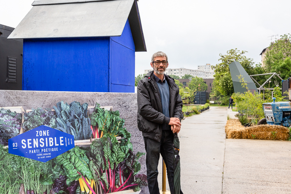 Chief gardener Franck Ponthier standing at the entrance to the Sensitive Zone, Urban Farm of Saint-Denis.   L'inauguration de la Ferme Urbaine de Saint-Denis le 11 mai 2019.  Zone Sensible / Parti Poétique et la Ferme Ouverte de Saint-Denis.