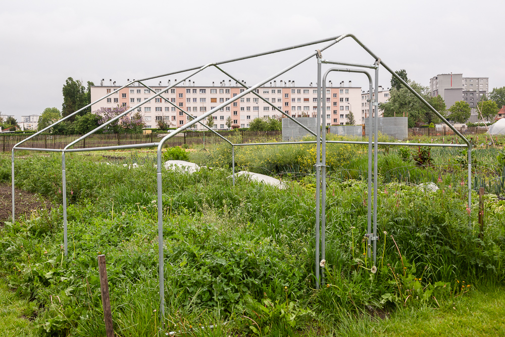 Greenhouse framework in the garden of the Sensitive Zone, Seine-Saint-Denis.  L'inauguration de la Ferme Urbaine de Saint-Denis le 11 mai 2019.  Zone Sensible / Parti Poétique et la Ferme Ouverte de Saint-Denis.