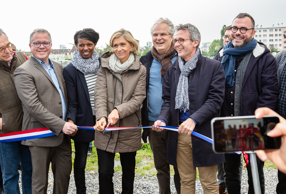 President of the IDF region (Valérie Pécresse) cuts the ribbon to inaugurate the Urban Farm of Saint-Denis with Saint-Denis Mayor (Laurent Russier - holding ribbon left) and President of the Seine-Saint-Denis Departmental Council President (Stéphane Troussel - holding ribbon right).