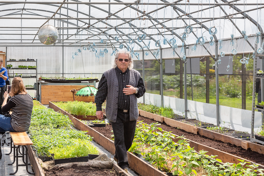 Enjoying the fanfare, retired vegetable farmer René Kersanté poses under the disco ball in the greenhouse of the Sensitive Zone.