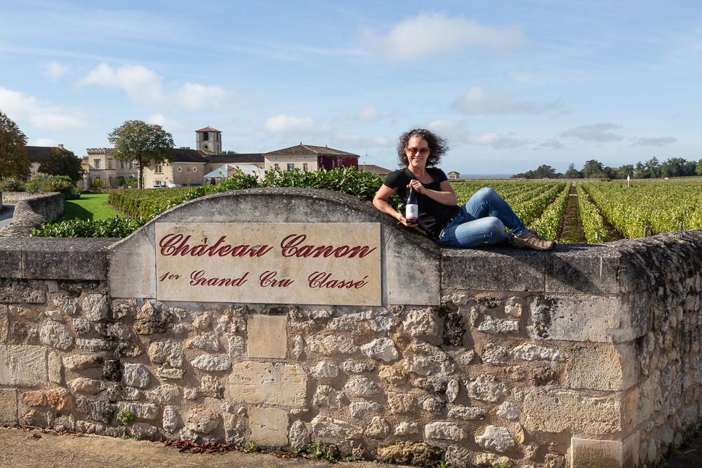 Elise Prudhomme posing with a bottle of Three Feathers Estate Pinot Noir in front of the vineyards at Chateau Canon 1er Grand Cru Classe, Saint Emilion in the Bordeaux wine region of France.